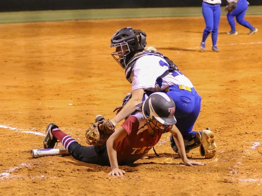 Tate's Avery Beauchaine (17) slides safely into home plate to score a runa gainst Washington during the district semi-final game at Tate High School on Tuesday, April 25, 2017.