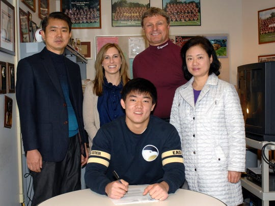 Younghoe Koo signing his National Letter of Intent for Georgia Southern University in 2013.  With him are (left to right) his father, Hyun Seo Koo, his guidance counselor Lauren Hellman, his coach Chuck Johnson and his mother Seung Mae Choi.