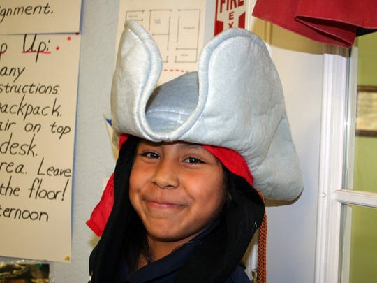 A grinning AHA student dresses the part of a history