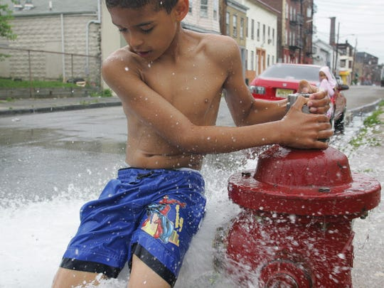In this July 9, 2008 file photo, Wilson Dominguez, 7, of Paterson, cools off with the open hydrant.
