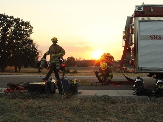 Volunteer firefighters Ethan Neve, left, and Ben Sperber, ready equipment for a training exercise in Palo Cedro.