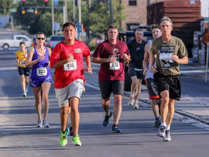 Runners make their way through downtown Pensacola during