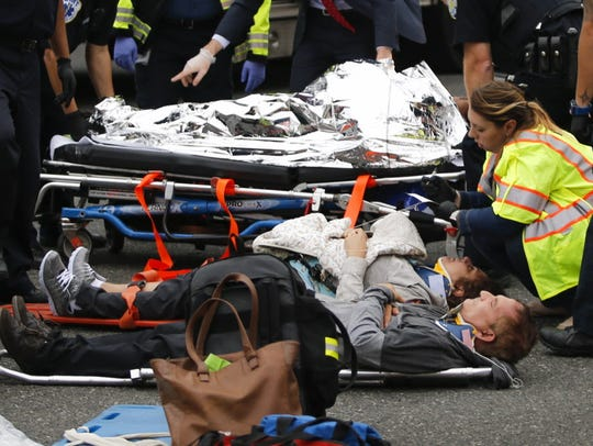 People are treated for their injuries on the street