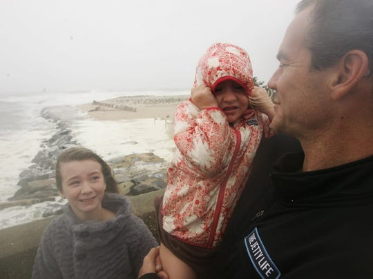 Morgan Iglay 10 watches her sister, Seton Iglay 4, who is held by their father, Dan Iglay of Spring Lake on the Route 71 bridge connecting, Belmar and Avon-By-The-Sea as water covered the dunes and winds topped 40 miles per hour on Oct. 29, 2012.