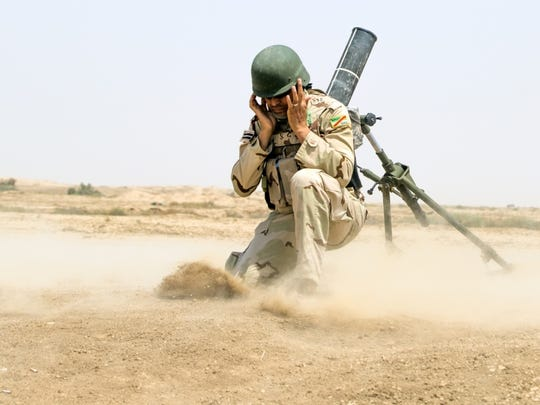 An Iraqi army soldier faces away and protects his ears from the blast as a 120 mm mortar fires during indirect fire training led by the Spanish army at the Besmaya Range Complex.