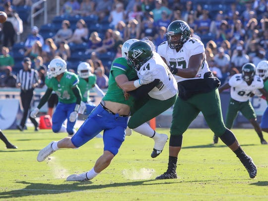 UWF's John Williamson (30) hits Delta State quarterback Collin Willis (14) right after the ball is released at Blue Wahoos Stadium on Saturday, October 14, 2017.
