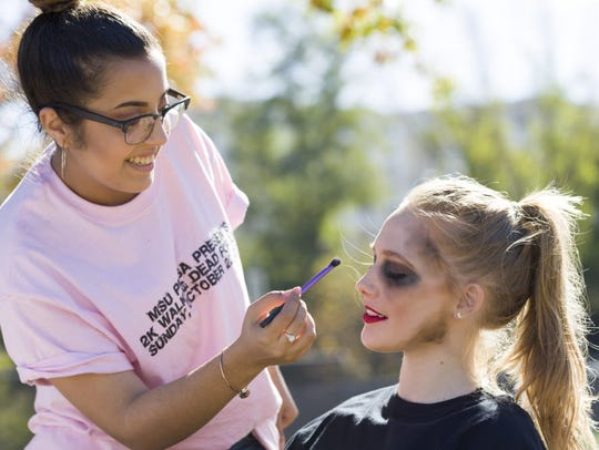 "Stephanie Michael, left, a Montclair State University junior from East Brunswick, zombie-izes freshman Amanda Peacock of Williamstown in preparation for Sunday's Montclair State 2K ""Walking Dead for Life"" event to benefit Hackensack's John Theurer Cancer Center."