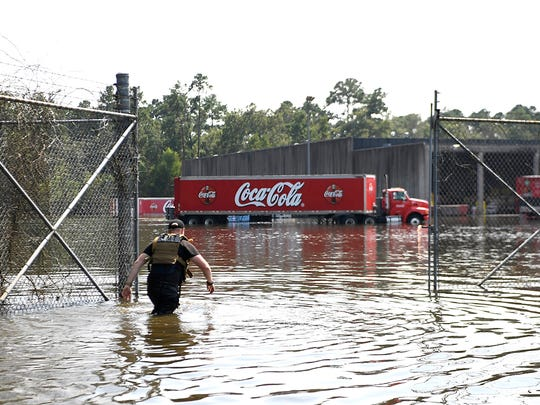 Sam Byers, an EMT from Arlington, Texas, wades past the gates of the Coca-Cola warehouse to get uncontaminated water in Beaumont, Texas, on Saturday, September 2, 2017.