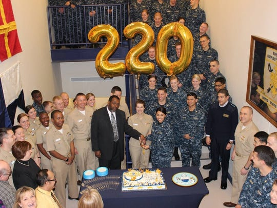 (NEWPORT, R.I.) Capt. Kristen Fabry, commanding officer, Navy Supply Corps School (pictured center) along with staff and students celebrate the 220th birthday of the Navy Supply Corps in March 2015. The supply corps provides the Navy with items essential to the operations of ships, aircraft, facilities and services of military personnel and their families.