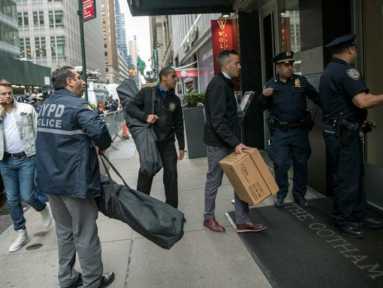 A pedestrian, left, watches as members of the New York