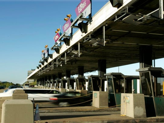 IN this file photo, cars drive through the toll booths on the New Jersey Turnpike in Woodbridge, N.J.