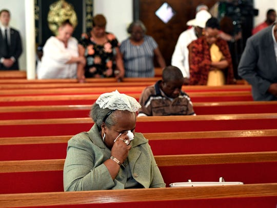 A woman weeps during mass at Galilee Baptist Church