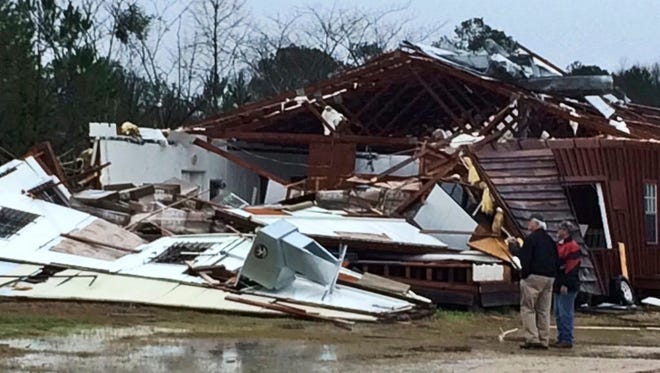 People survey damage to a business off Mississippi Highway 18 in Sylverana, Miss., Monday, Feb. 15, 2016, after severe weather affected south Mississippi. No injuries were reported in the storm. Officials are investigating reports of at least two possible tornadoes that accompanied a line of thunderstorms across central and southern Mississippi Monday.