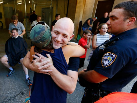 Reggie Crowley gives a hug to retired Randolph Ptl. Michele Edelman as Randolph police officers shave their heads in support of officer Crowley who lost his hair after chemotherapy.  July 16, 2018. Randolph, New Jersey