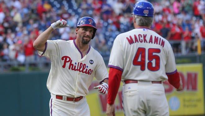 Phillies right fielder Jeff Francoeur high-fives third base coach Pete Mackanin after hitting a grand slam home run Saturday against the San Francisco Giants.