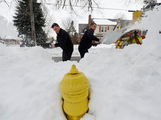 York Area United Fire and Rescue firefighters Patrick Mooney, left, and Chad McCullough clear snow around a fire hydrant on the first block of South Harlan Street in Springettsbury Township. Firefighters have been going out since Saturday checking on and clearing snow around the hydrants in their area.