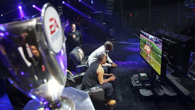 """NFL players LeSean McCoy and Cam Newton compete in """"EA Sports Madden Bowl XX"""" as host Drew Brees watches in New York."""