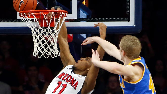 Arizona guard Allonzo Trier (11) is fouled by UCLA center Thomas Welsh during the first half of an NCAA college basketball game Friday, Feb 12, 2016, in Tucson, Ariz.