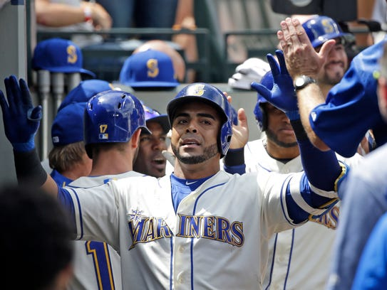 Nelson Cruz is congratulated by his teammates after