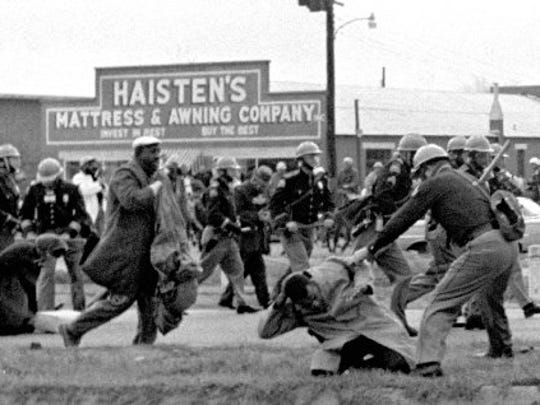 "In this March 7, 1965, file photo, state troopers use clubs against participants of a civil rights voting march in Selma, Ala. At foreground right, John Lewis, chairman of the Student Nonviolent Coordinating Committee, is beaten by a state trooper. The day, which became known as ""Bloody Sunday, "" is widely credited for galvanizing the nation's leaders and ultimately yielded passage of the Voting Rights Act of 1965."