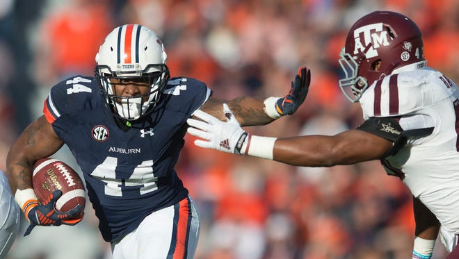 Auburn running back Cameron Artis-Payne (44) stiff arms Texas A&M linebacker Justin Bass (43) during the NCAA football game between Auburn and Texas A&M on Saturday, Nov. 8, 2014, in Auburn, Ala.