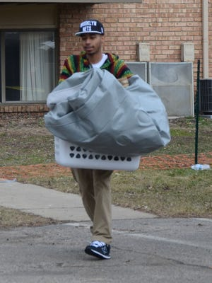 Detwan Williams leaves the burned-out Arbors apartment building with some of his personal belongings on Thursday.