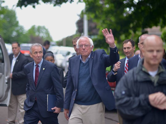 Sen. Bernie Sanders waves to supporters after addressing the news media on the front laws of his Burlington home on Sunday, June 12, 2016. The news conference followed a meeting with  members of his family, advisers and supporters.