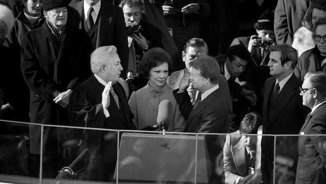 Jimmy Carter, right, is taking the oath of office to become the 39th President of the United States from Supreme Court Chief Justice Warren E. Burger, left, as wife Rosalynn holds the Bible for the inaugural ceremonies in Washington D.C. Jan. 20, 1977.