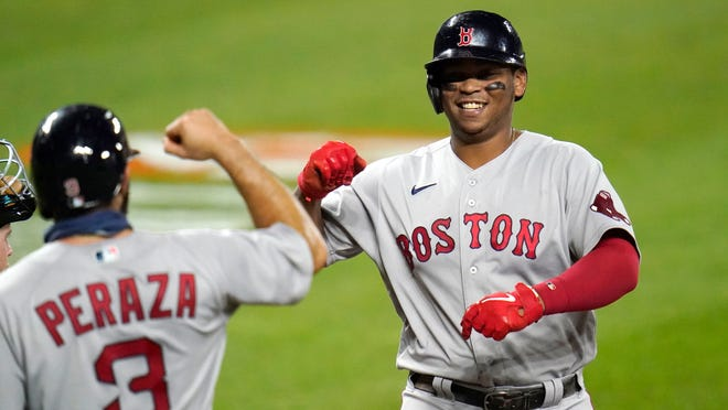 Red Sox base runner Rafael Devers, right, is greeted near home plate by Jose Peraza after Devers hit a three-run homer during the fifth inning Friday night in Baltimore.