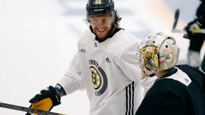 Boston Bruins right wing David Pastrnak jokes with goalie Daniel Vladar as they skate to the bench at the NHL hockey team's camp on Wednesday, July 15, 2020, in Boston.