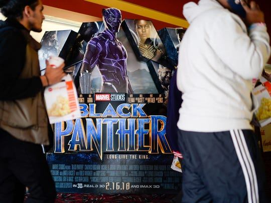 Students walk past a 'Black Panther' poster as a special screening is set to begin as part of an event organized by Campbell Soup Company's Black Resource Group Thursday, Feb. 15, 2018 at AMC Loews in Cherry Hill, N.J.