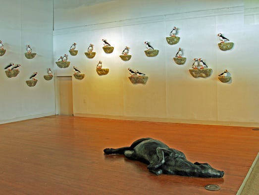 "On the walls, a display of puffin sculptures by Peter Morgan, titled ""I Think There's a Puffin Among Us."" On the floor is ""Suprise"" by Darla Jackson, a lifesized, prone, doe."