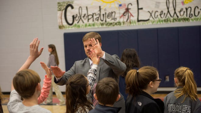 Lewisburg Middle School Principal Brad Meadows high-fives students during an event at LMS Friday in Olive Branch honoring DeSoto County schools. The district was one of nine in Mississippi to earn the top A ranking by the state, and LMS was the top-ranked middle school in the state.