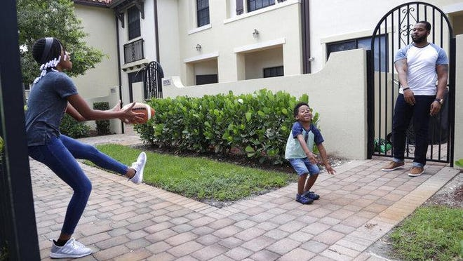 D.J. Boldin, right, throws a football on June 16 with his children Madison, 10, left, and Dallas, 4, center, outside of their home in Miramar. Boldin is the football coach at Pahokee High School, a predominantly black school located alongside Lake Okeechobee in Florida. Recent events have given Boldin an opportunity to use his position to prepare his players for the challenges they will face when they leave the bubble that is their small town.