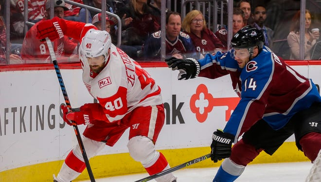 Henrik Zetterberg and Blake Comeau chase the puck behind the net during the second period Sunday in Denver.