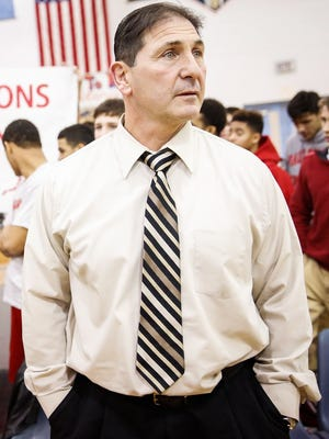 Paulsboro wrestling coach Paul Morina stands at the edge of the mat as his team holds a banner behind him recognizing his 600th career win following Paulsboro's win at Overbrook High School Monday, January 12, 2015 in Pine Hill. MATT STANLEY