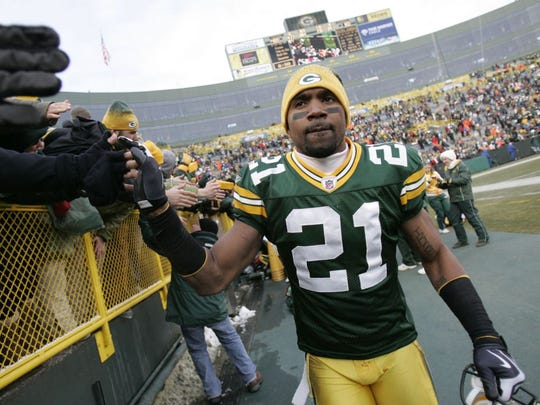 Green Bay Packers cornerback Charles Woodson celebrates with fans following a 2009 victory against the Seattle Seahawks at Lambeau Field.