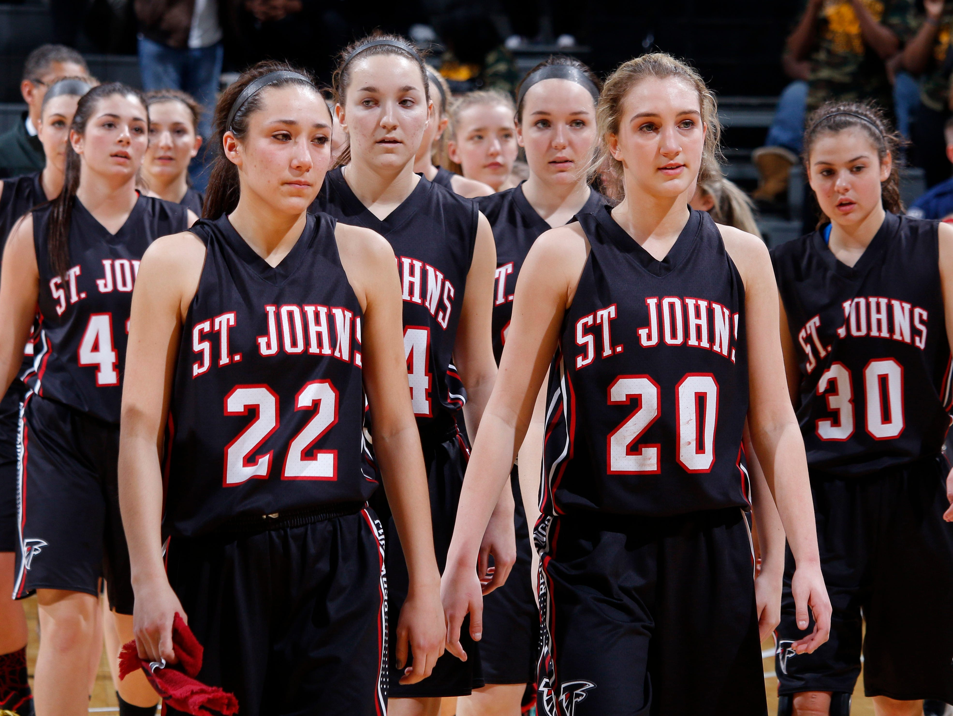 St. Johns players, including Erika Ballinger (22) and Maddie Maloney (20), walk off the court following their loss to Detroit King in their MHSAA Class A semifinal game Friday, March 18, 2016, at the Breslin Center in East Lansing. St. Johns fell 56-48.