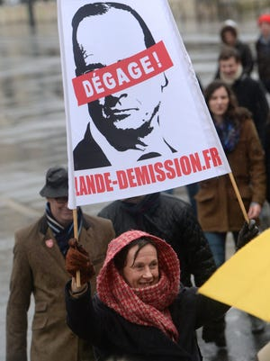 """A woman holds a banner dispaying a portrait of the French President Francois Hollande with the phrase """"Get out!"""" during a demonstration called by the Collective """"Day of Wrath"""", supported among others by the conservative Printemps Francais (""""French Spring"""") movement and the fundamentalist christian group Civitas, to protest against the French President's policy, on Jan. 26, 2014 in Paris."""