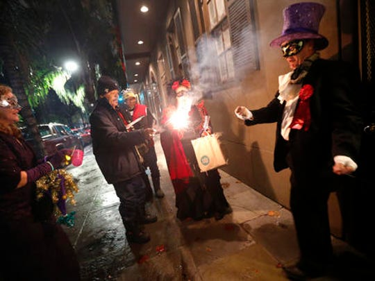 """Members of the """"Societe des Champs Elysee"""" light fireworks on their way to a bar, after riding the Rampart-St. Claude street car line, which just opened last fall, to commemorate the official start of Mardi Gras season, in New Orleans, Friday, Jan. 6, 2017. Wearing masks and festive costumes, they honored their king and queen at a neighborhood bar and danced as a brass band played """"Carnival Time,"""" before and after boarding their red street car."""