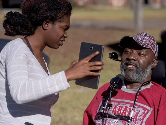 Mellonie Etheridge holds up a tablet as David Harris