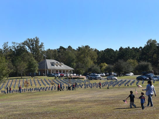 People place flags on veterans graves Friday at the