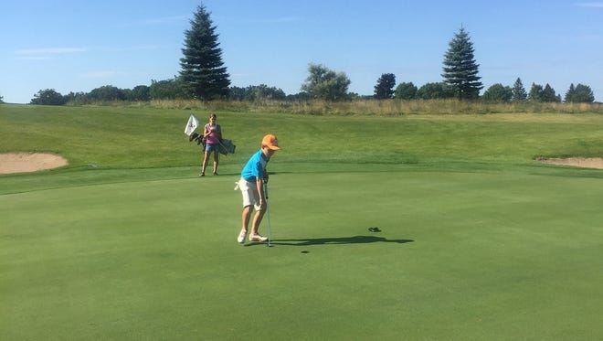 Clearwater's Luke Ashbrook putts on the green as his mother, Victoria, looks on.