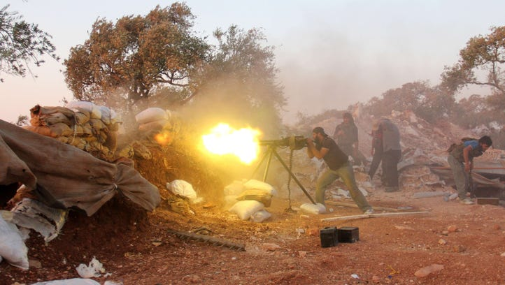 A rebel fighter fires heavy artillery during clashes