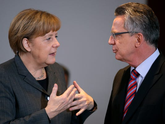 German Chancellor Angela Merkel, left, talks to German Interior Minister Thomas de Maiziere, right, during the beginning of the weekly cabinet meeting at the chancellery in Berlin, Germany, Wednesday, Nov. 12, 2014. (AP Photo/Michael Sohn)