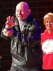 James von Raschke, better known by his ring name as Baron von Raschke, eggs on the crowd with his signature claw while escorted onto the stage by Dawn and Sherri Lisowski during a fundraising meet-and-greet and storytelling session at the South Milwaukee Performing Arts Center in 2018.