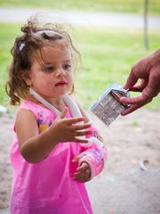 2-year-old Magdalena Kennedy receives some chocolate milk at Young Park from 17-year-old volunteer Jalen Guerrero as part of a free lunch program organized by Families and Youth, Inc., June 1, 2016.
