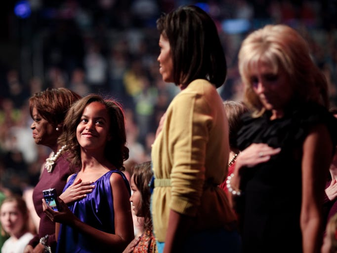 Malia Obama, left, looks up at her mother Michelle
