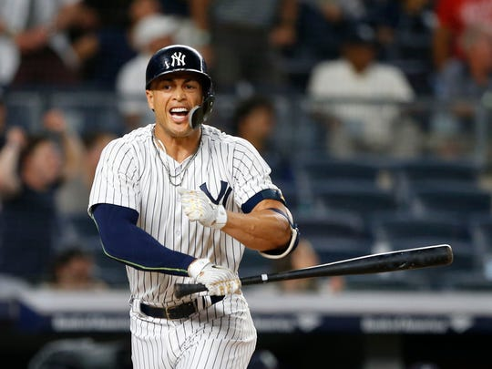 New York Yankees left fielder Giancarlo Stanton (27) celebrates after hitting a walk off home run against the Seattle Mariners at Yankee Stadium.