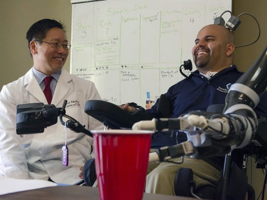 Dr. Charles Y. Liu, left, a neurosurgeon at the University of Southern California, laughs with patient Erik Sorto in Pasadena, Calif. Liu led a team of doctors that implanted tiny chips into Sorto's brain in 2013 to allow him to control a robotic arm using his thoughts.